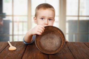 boy holding an empty bowl at the kitchen table